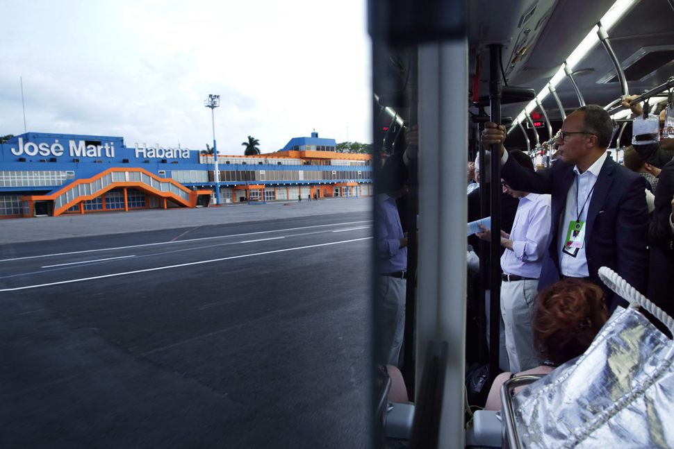 Journalists, including NBC news anchor Lester Holt, ride in a bus at José Martí International Airport upon thei