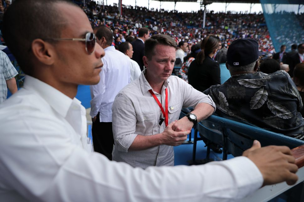 A Cuban security agent works with a member of the U.S. Secret Service at Havana's Estadio Latinoamericano, where Ca