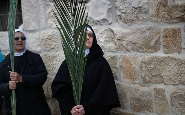 Christian nuns carry palm branches duringa procession forPalm Sunday at the Mount of Olives in Jerusalem on March