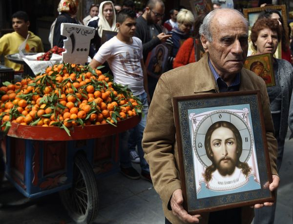 A Greek Orthodox Christian man holds an icon depicting Jesus Christ as he walks with Christian Melkites during a joint proces