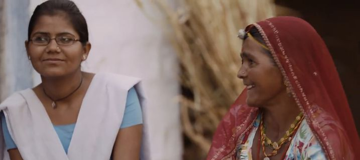 In the video, Pramilla sits with her mother, who never went to school.