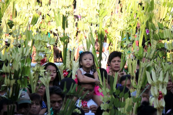 """A group of Catholic devotees hold their """"palaspas"""" (palm leaves) while listening to the priest onPalm Sunday, March 20,"""