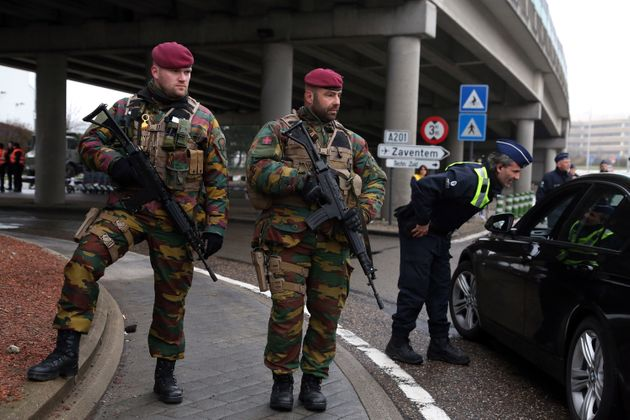 Belgian soldiers stand guard as police check vehicles outside of the closed Brussels Zaventem airport...