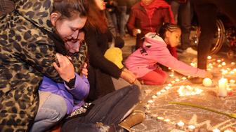 BRUSSELS, BELGIUM - MARCH 22:  Two young girls cry as people gather to leave tributes at the Place de la Bourse following today's terrorist attacks on March 22, 2016 in Brussels, Belgium. At least 31 people are thought to have been killed after Brussels airport and a Metro station were targeted by explosions. The attacks come just days after a key suspect in the Paris attacks, Salah Abdeslam, was captured in Brussels.  (Photo by Sylvain Lefevre/Getty Images)