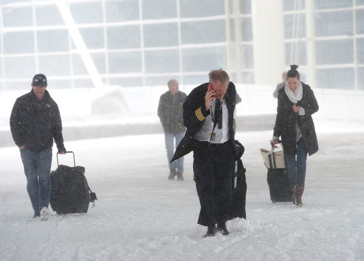 DENVER, CO - March 23: Airline passengers and a pilot make their way to the Westin Hotel at the Denver International Airport in bitter winds and heavy snow March 23, 2016. (Photo by Andy Cross/The Denver Post via Getty Images)