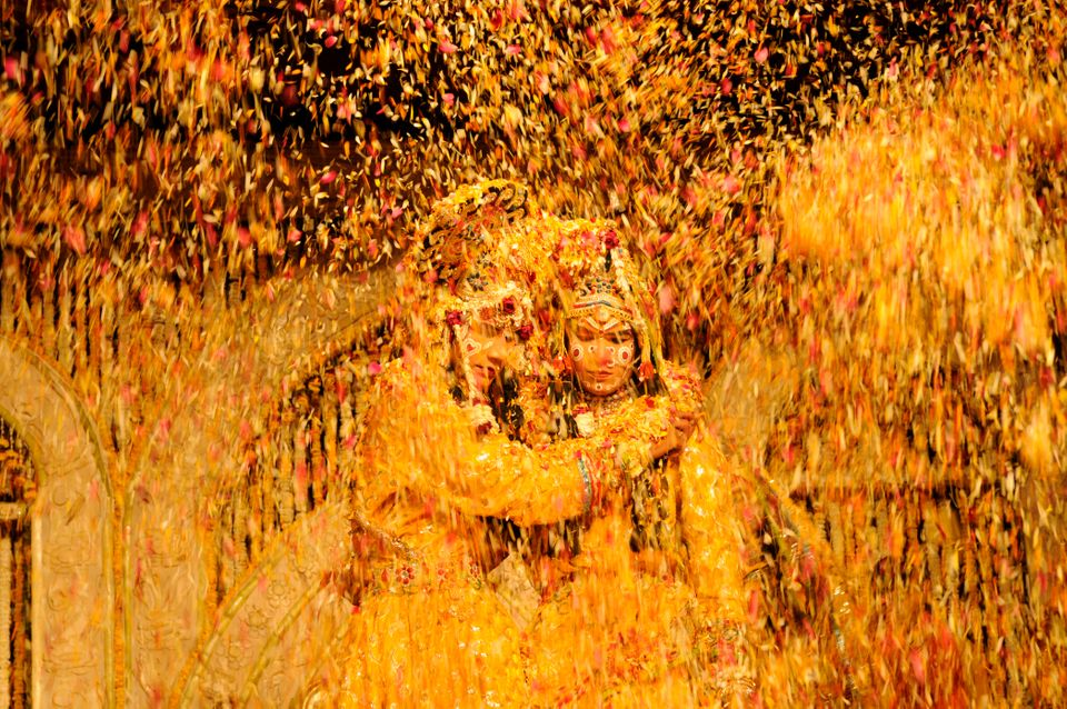 Indian artists dressed up as Hindu Lord Krishna and his consort Radha are showered with flower petals...