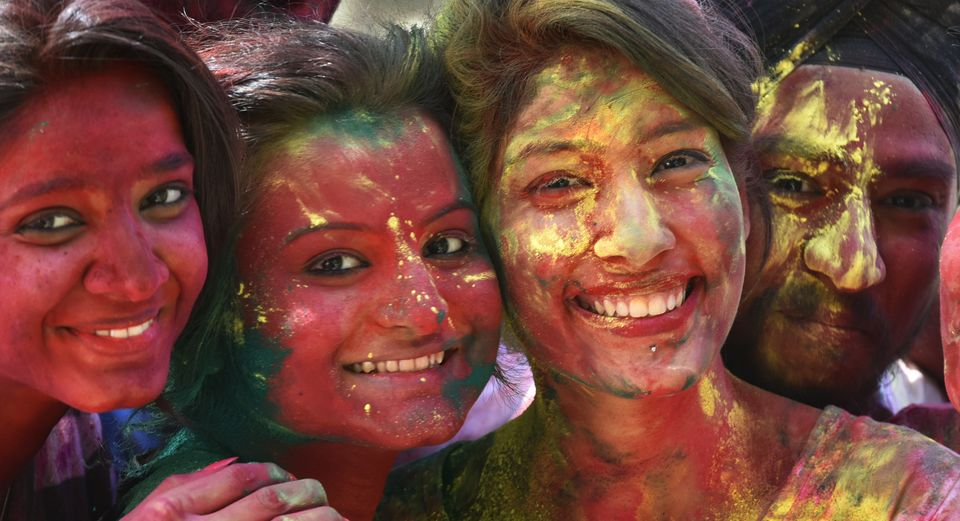 Students apply Gulal (dry colored powder) on each other before the Holi festival outside YMCA in New