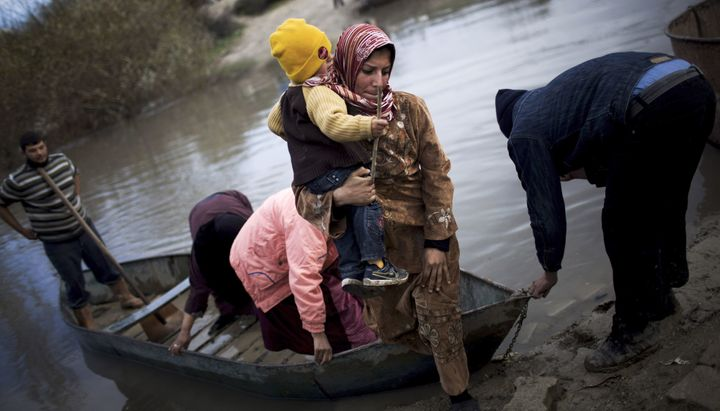 Syrian refugees cross from Syria to Turkey by the Orontes river, near the village of Hacipasa, Turkey on Dec. 8, 2012.
