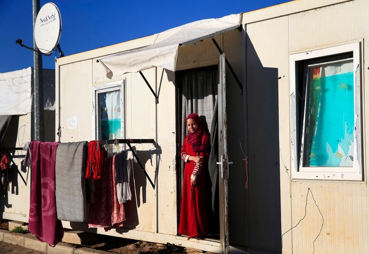 A Syrian refugee woman stands at the entrance of the container where her family is living, at the Oncupinar camp for Syrian r