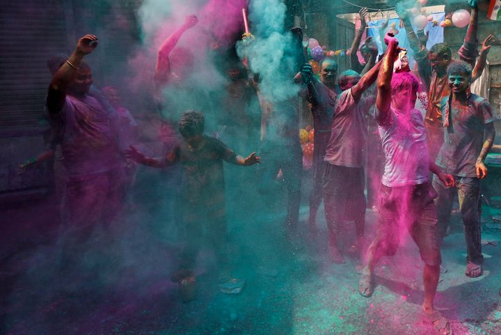 Men dance as others throw colored powder on them during Holi celebrations in Kolkata, India, March 24, 2016.