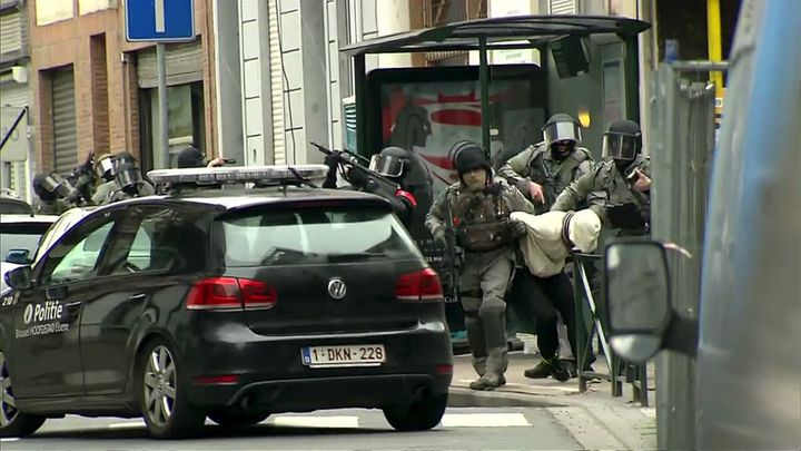 This still image taken from a video shows armed Belgian police apprehending a suspect in Molenbeek, Belgium, on March 18.