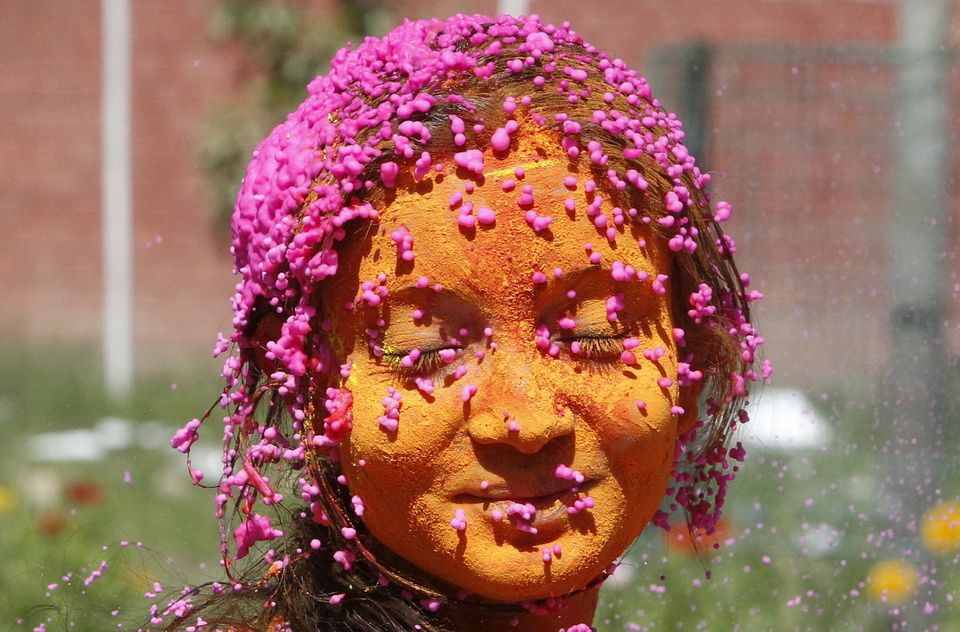 A student with her face smeared in colored powder, celebrates Holi at a university campus in Chandigarh, India March 23, 2016