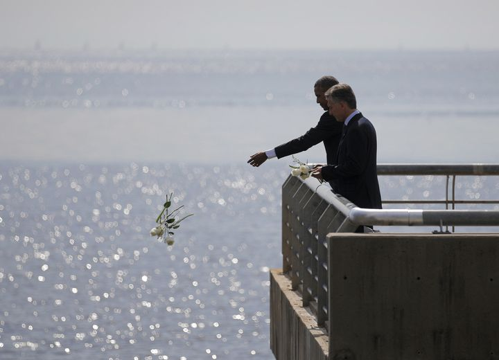 President Barack Obama and Argentina's President Mauricio Marci throw flowers into the River Plate to honor victims of the Di