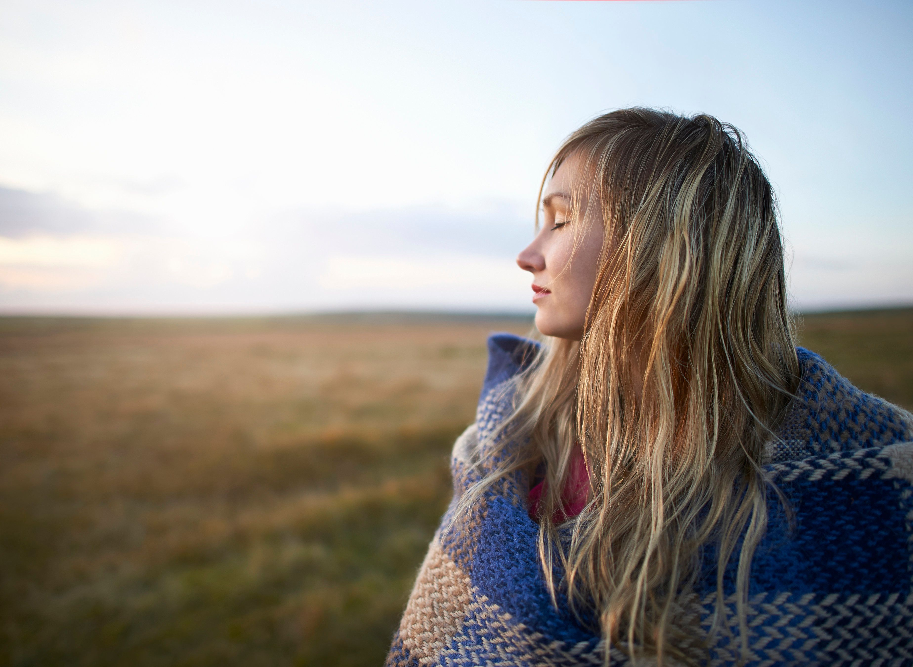 A woman stands with her eyes closed and wrapped in a blanket on a moorland.