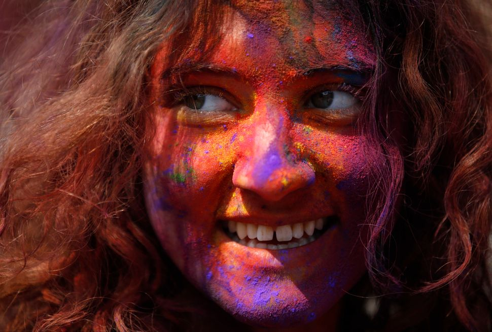 A woman with colored powder smeared on her face smiles as she celebrates Holi, the Festival of Colours, in Kathmandu, Nepal.