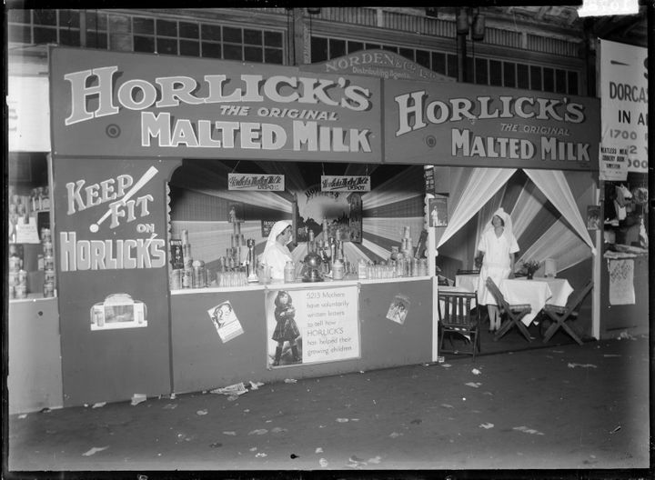"A stall at a 1930 tradeshow advertises Horlick's malted milk as a health tonic: ""5213 mothers have voluntarily written letters to tell how HORLICK'S has helped their growing children,"" a sign states."