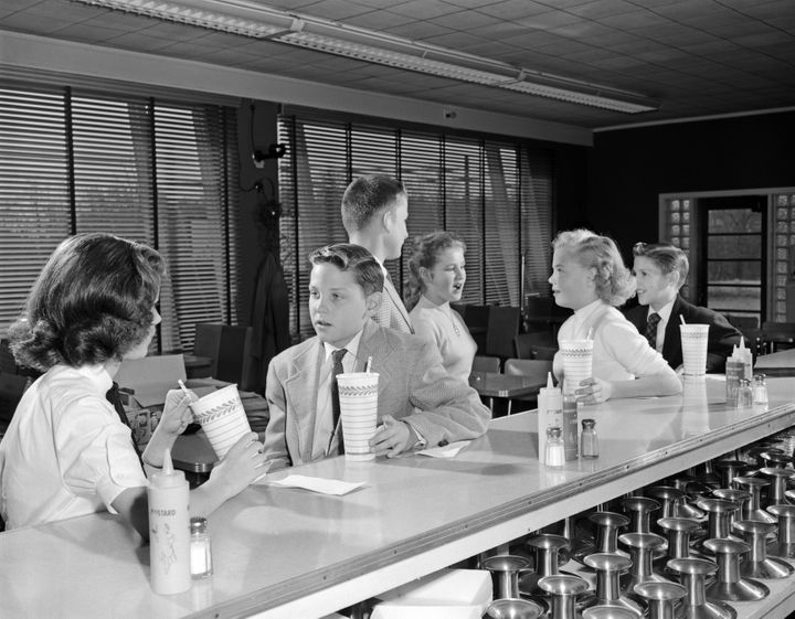 Teens sit at a soda fountain in the 1950s to drink milkshakes.