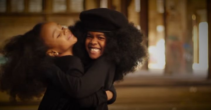 Two young black girls embrace each other in a warm hug in Johnson's video.
