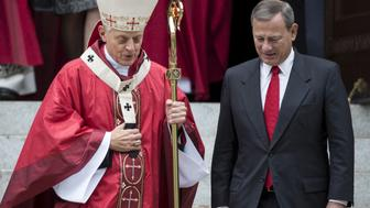 Supreme Court Justice John Roberts (R) speaks with Cardinal Donald Wuerl (L), archbishop of Washington, as he departs from St. Matthews Catholic Church after attending the 63rd annual Red Mass on the Sunday before the U.S. Supreme Court's new term opens in Washington, October 4, 2015. REUTERS/Joshua Roberts