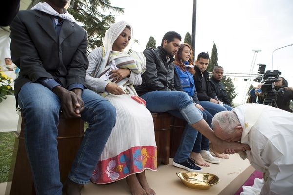 Pope Francis kisses the foot of a refugee.
