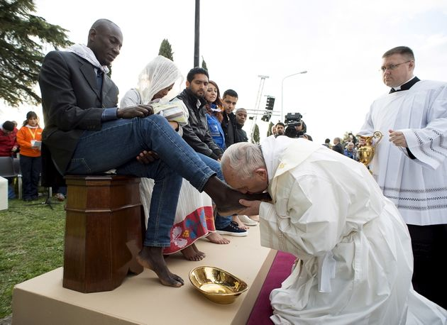 Pope Francis kisses the foot of a refugee during the foot washing ritual at the Castelnuovo di Porto...