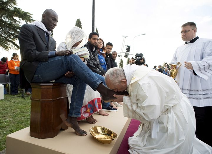 Pope Francis kisses the foot of a refugee during the foot washing ritual at the Castelnuovo di Porto refugees center near Rom