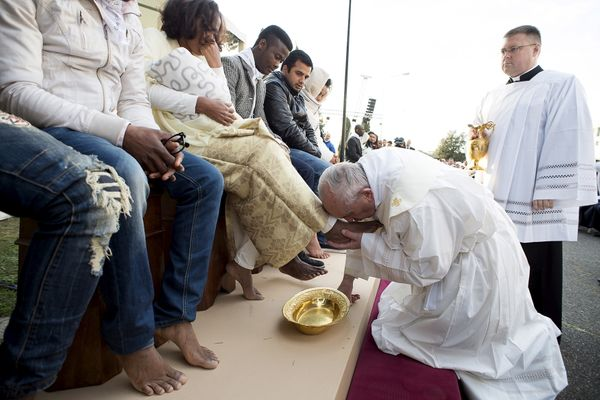 Pope Francis kisses the foot of a refugee during the foot washing ritual at the Castelnuovo di Porto refugees center.