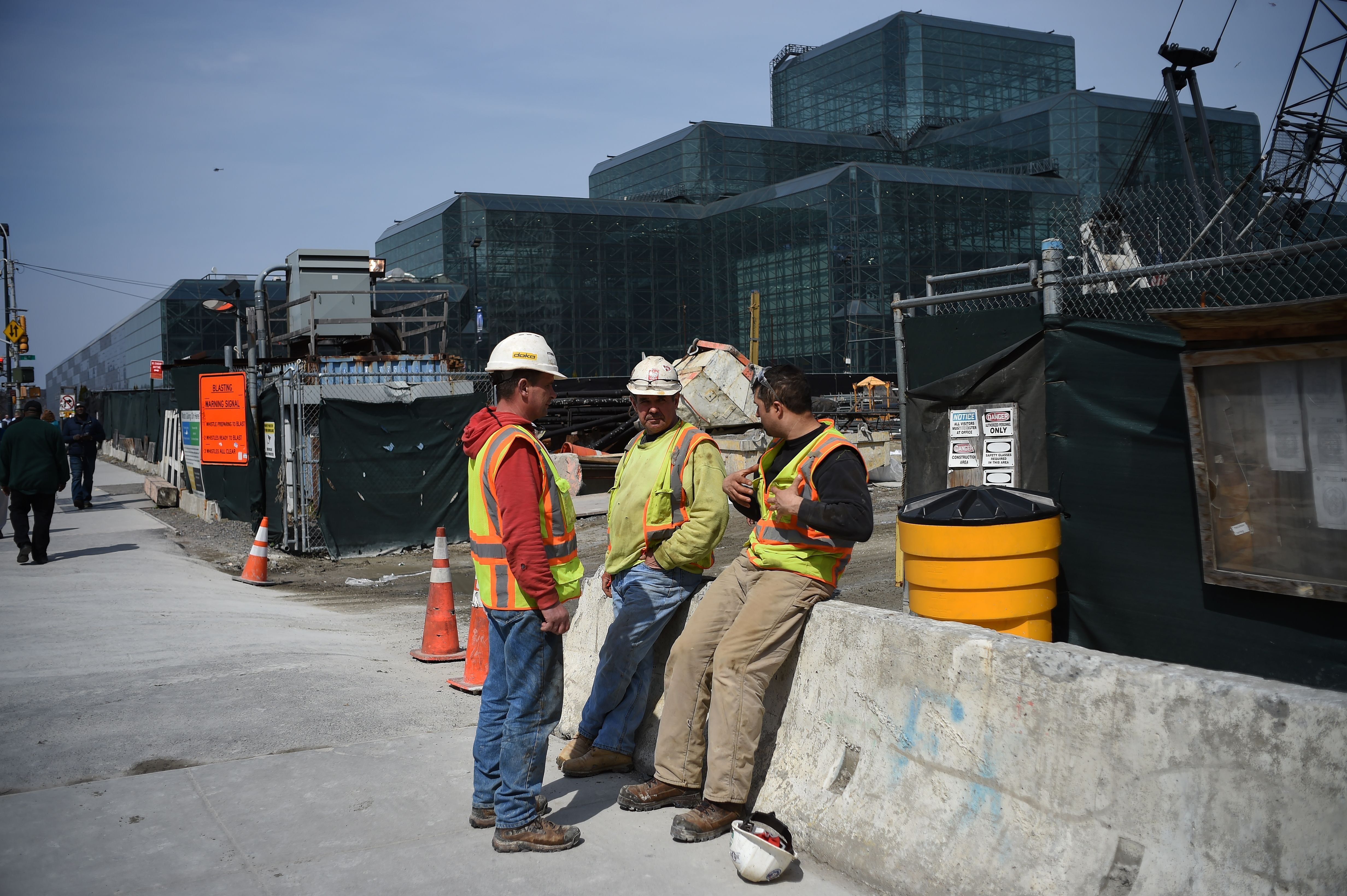 Construction workers chat during their break at a building site in New York on March 24, 2016. Latinos are over-represented i