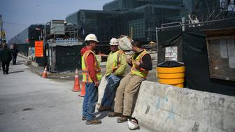 Construction workers chat during their break at a building site in New York on March 24, 2016.  / AFP / Jewel SAMAD        (Photo credit should read JEWEL SAMAD/AFP/Getty Images)