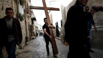 A Christian pilgrim carries a wooden cross along the Via Dolorosa (Way of Suffering) in Jerusalems Old City during the Good Friday procession on March 25, 2016. Many Christian pilgrims took part in processions along the route where according to tradition Jesus Christ carried the cross during his last days.   / AFP / THOMAS COEX        (Photo credit should read THOMAS COEX/AFP/Getty Images)