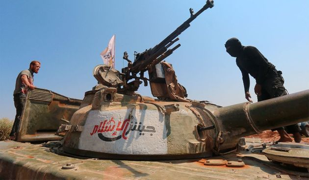 Rebel forces from Jaish al-Islam stand on a tank near a frontline in Syria last August. The group's leader...