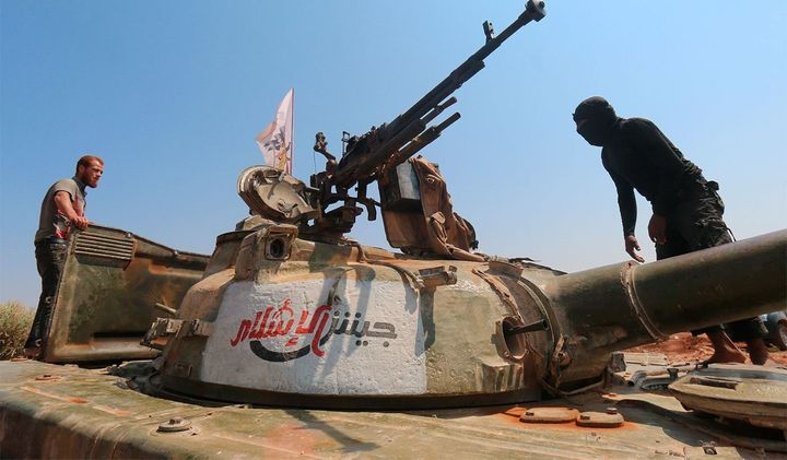 Rebel forces from Jaish al-Islam stand on a tank near a frontline in Syria last August. The group's leader was&nbsp