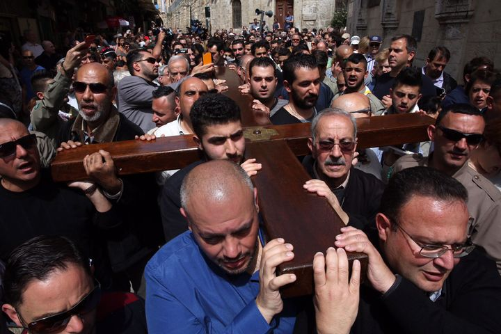Arab Christian pilgrims carry a wooden cross along the Via Dolorosa (Way of Suffering) in Jerusalem's Old City during the Goo