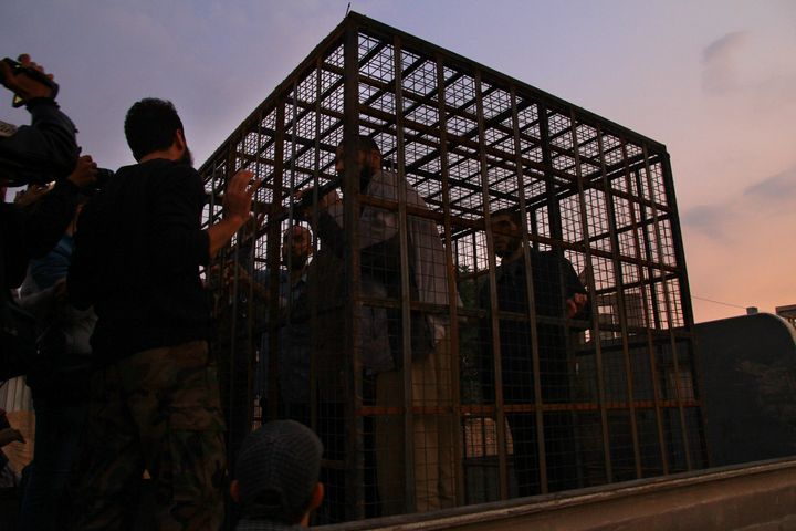 Syrians are seen inside imprisoned in a cage in Douma last August, an area held by Jaish al-Islam. Syrians say tort