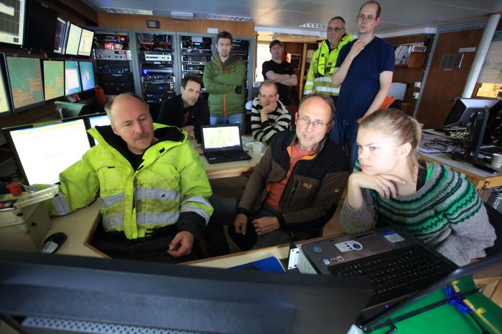 Peter Linke (center), scientists and engineers gather around video monitors in the ship's instrument room to monitor the desc