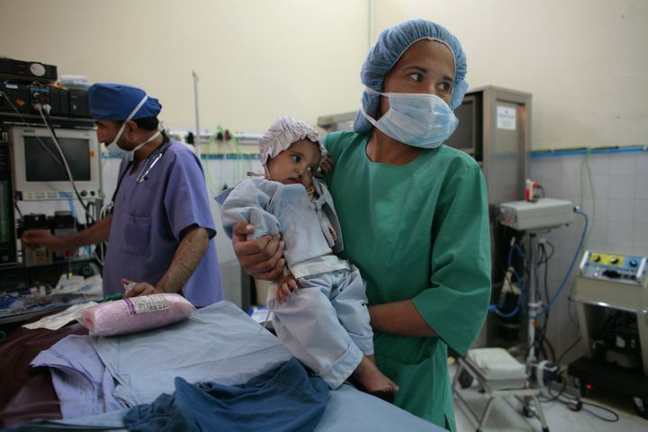 KABUL, AFGHANISTAN - NOVEMBER 9: Subada, 18 months, is held by a nurse before her cleft lip and palate operation at a special