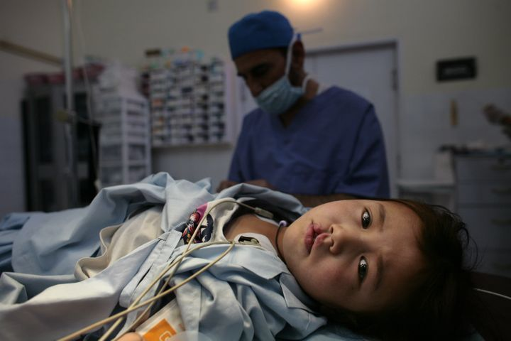 KABUL, AFGHANISTAN - NOVEMBER 9: Sakima, 7, lays on the operation table before surgery starts to fix her right cleft lip at a