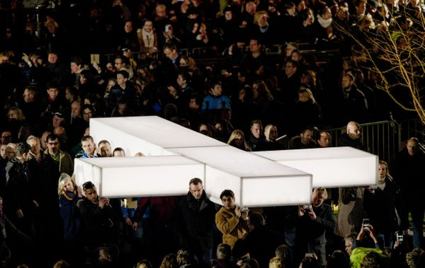 People carry a giant white cross during The Passion, a Dutch passion play, held on Maundy Thursday in Amersfoort, Netherlands