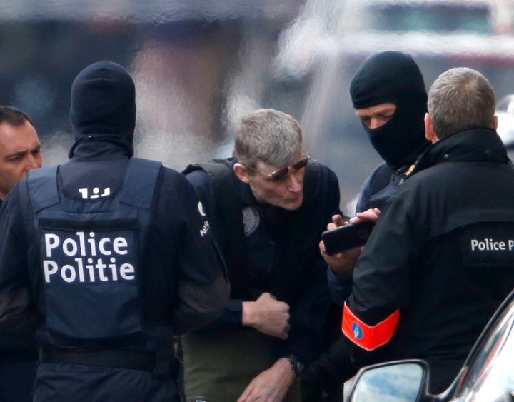 Belgian prosecutors charged three men with terrorism on Saturday. Above, police search people in Brussels after the attacks.