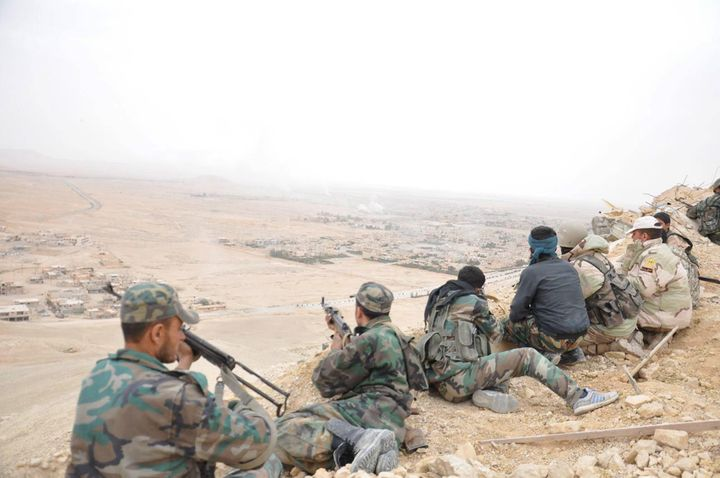 Forces loyal to Syria's President Bashar al-Assad take positions on a look-out point overlooking the historic city of Palmyra