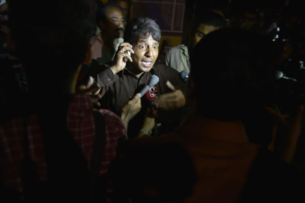 A Pakistani eye witness talks with media representatives at a bomb blast site in Lahore on March 27,...