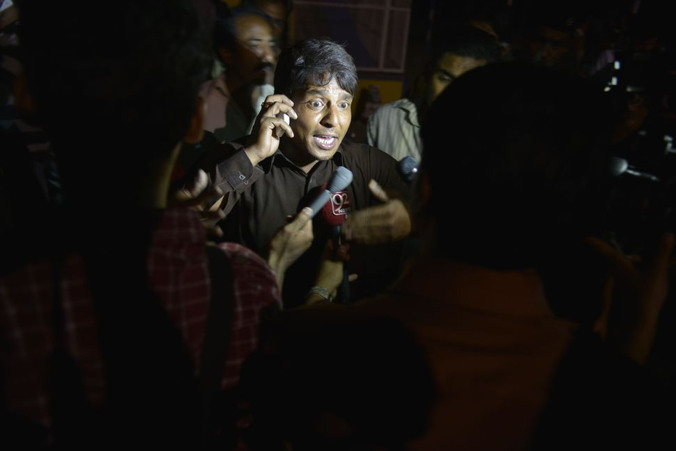 A Pakistani eyewitness talks with the media at the bomb blast site in Lahore.