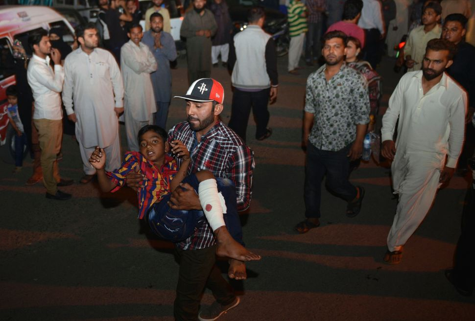 A Pakistani man carries an injured child to the hospital in Lahore on March 27, 2016.