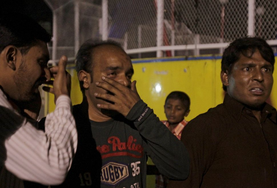 Men mourn relatives killed in a blast outside a public park in Lahore, Pakistan, March 27, 2016.