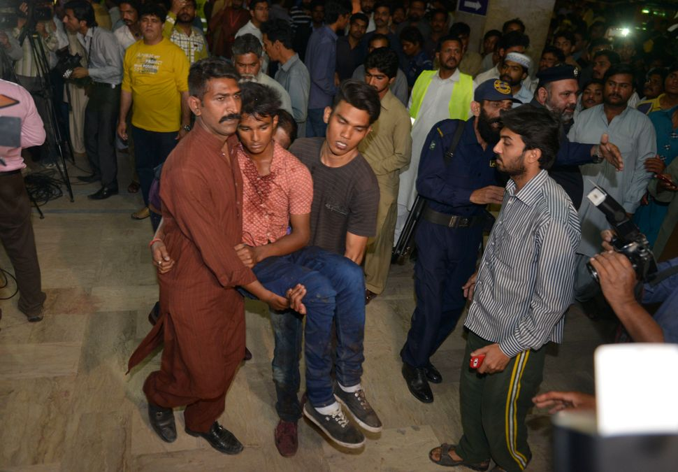 Relatives move an injured bomb blast victim into a hospital after a bomb blast in Lahore.