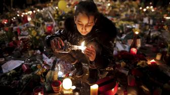 A girl lights candles as people pay tribute to the victims of Tuesday's bomb attacks, at the Place de la Bourse in Brussels, Belgium, March 26, 2016. REUTERS/Christian Hartmann      TPX IMAGES OF THE DAY