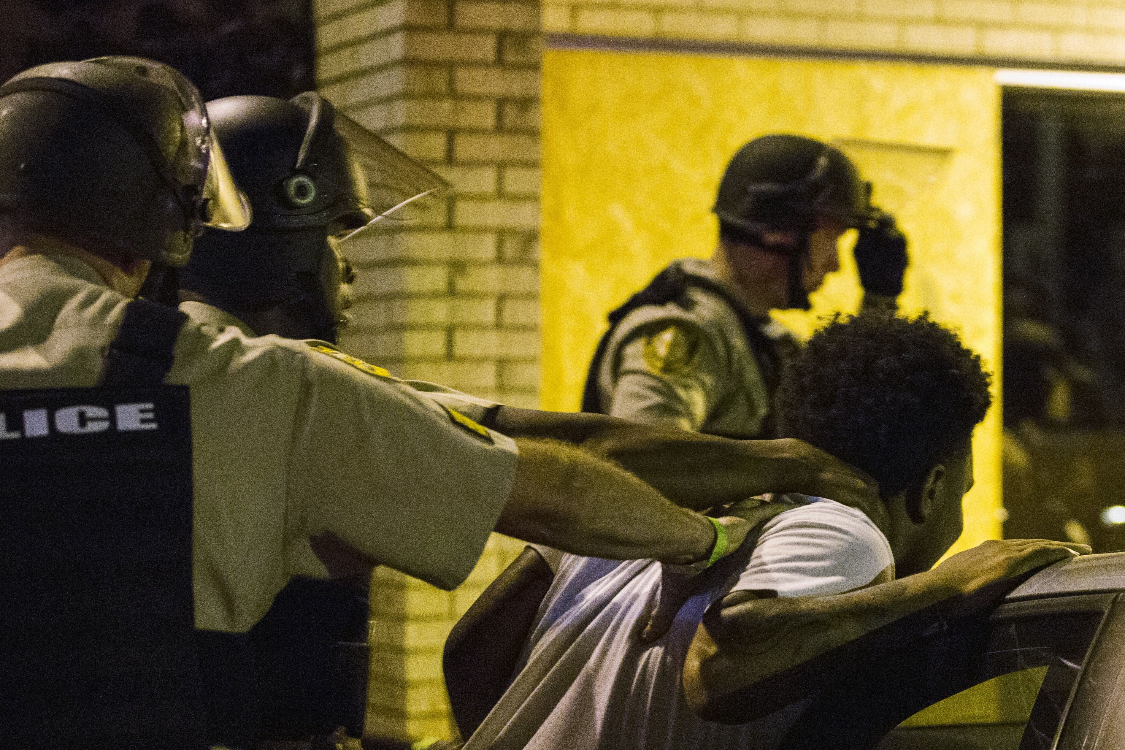 St Louis County police officers arrest an anti-police demonstrator in Ferguson, Missouri August 11, 2015. Police in riot gear clashed with protesters who had gathered in the streets of Ferguson early on Tuesday to mark the anniversary of the police shooting of an unarmed black teen whose death sparked a national outcry over race relations. REUTERS/Lucas Jackson