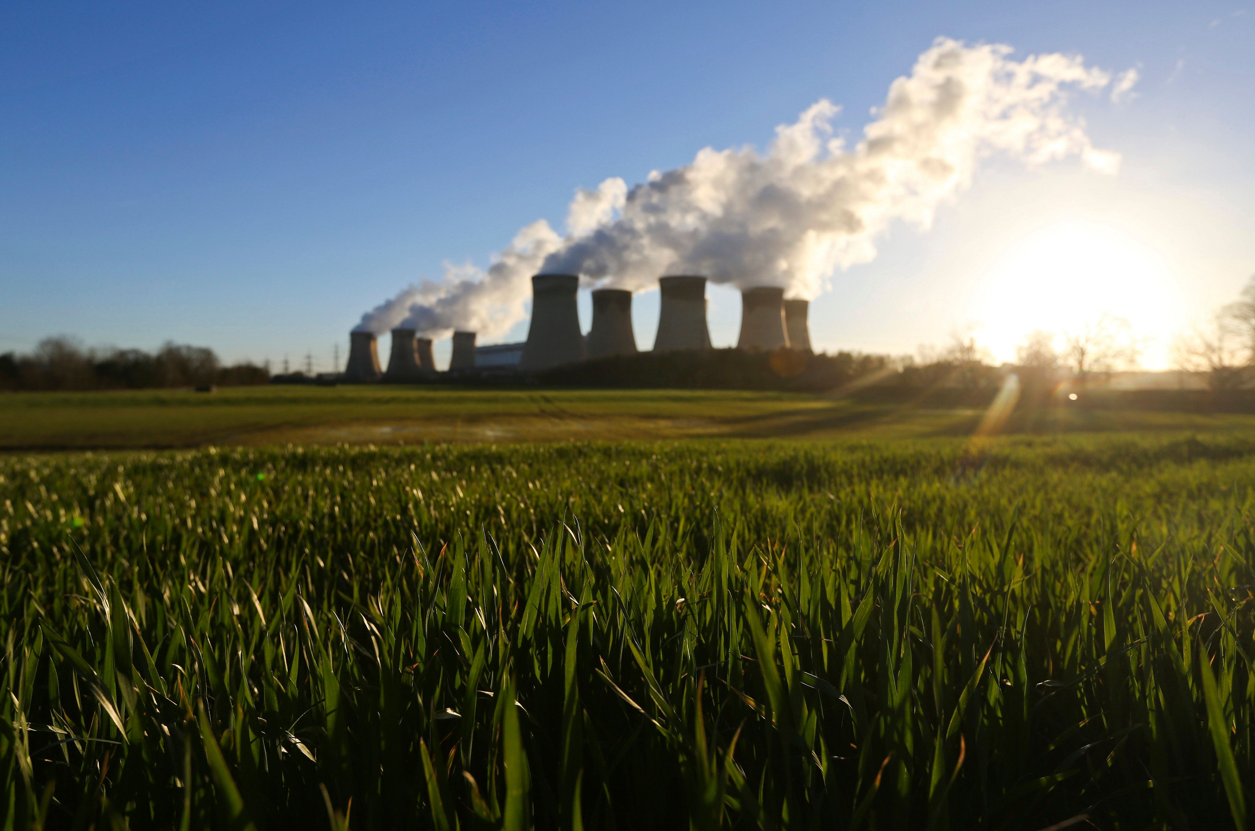 Agricultural crops grow in a farmer's field as vapour rises from cooling towers at Drax Power Station, operated by Drax Group Plc, in Selby, U.K., on Tuesday, March 11, 2014. Drax Group Plc, the operator of the U.K.'s biggest coal-fired power station, reported a 23 percent slump in full-year profit as carbon prices rose and it prepared to convert two more units to burn cleaner fuel. Photographer: Chris Ratcliffe/Bloomberg via Getty Images