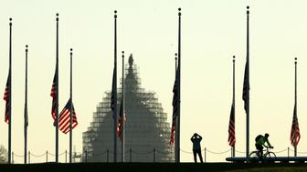 The dome of the U.S. Capitol is seen as flags fly at half staff at the Washington Monument on the National Mall in Washington November 16, 2015. U.S. President Barack Obama issued a proclamation ordering flags to fly at half staff as a mark of respect for victims of the Paris attacks.REUTERS/Kevin Lamarque