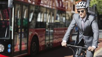 Young businessman riding bicycle by bus on street